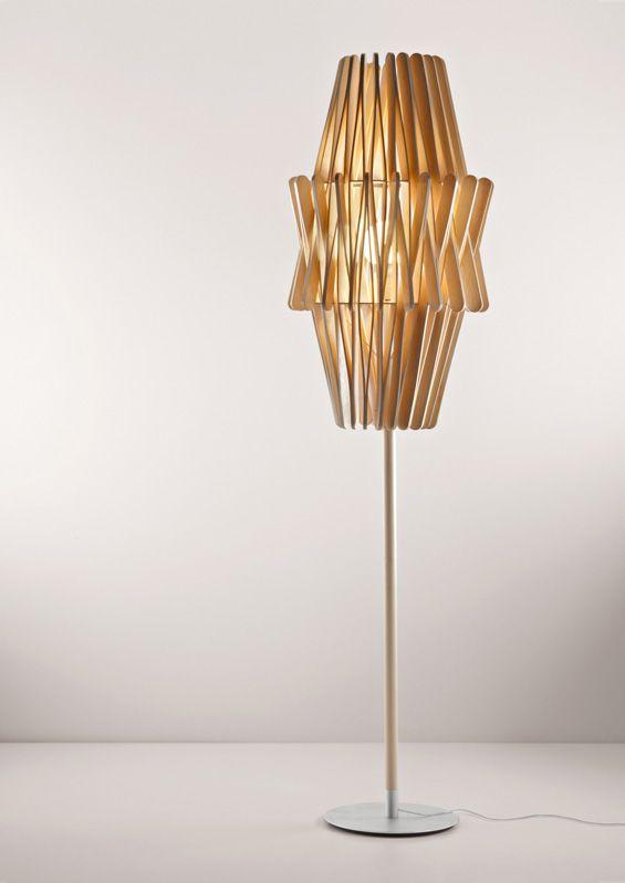 """Collection de lampes """"Stick"""" par Matali Crasset  Cette collection se compose d'une lampe de table, d'une lampe murale, de quatre lampadaires et de cinq suspensions. La structure de ces lampes s'articule autour de pièces de bois en forme de pince et répétées pour créer des abats jours graphiques et géométriques. Les bâtonnets bois diffusent une lumière douce et chaleureuse et les zones ajourées créent un subtil jeu de projection d'ombres portées."""