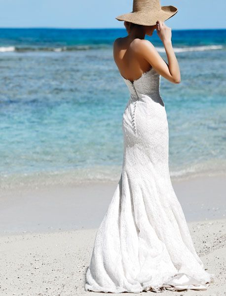 Sequin embroidered lace strapless trumpet gown with pearl buttons in back, about $1,168, by Allure Bridals. Woven hat by August Accessories.Photography by Jennifer Robbins / Hair and makeup: Cheyenne Timberio / Photographed in the British Virgin Islands