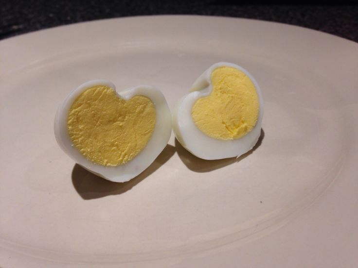 Hear shaped boiled eggs (Valentines). Need:- 2 x Boiled egg Cut corner (square edge) of a fruit juice carton Wooden kebab skewer Elastic bands 1-Peal the shell off the 2x boiled eggs 2-Put the two eggs lengthways in the edge of the fruit juice carton (this forms the V at the bottom of the egg) 3-Lay the kebab skewer along the length of the two eggs 4-Apply pressure on the eggs by securing the kebab skewer with elastic bands 5-Leave in the fridge for an hour 3-Place a pencil over the two eggs