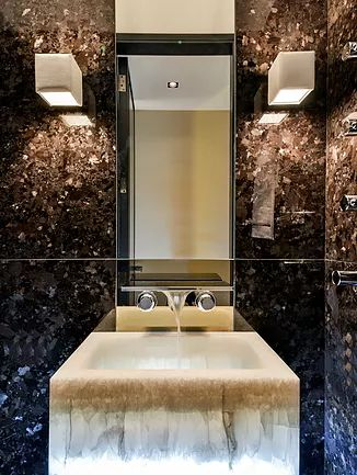 Cloakroom fitted with illuminated white onyx basin on Marron Cohiba marble by Privately owned investment and development company specialising in luxury bespoke refurbishments and independent strategic property consultancy.