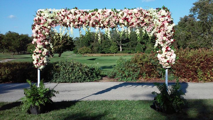 A showstopping outdoor ceremony at The duPont Country Club for Erika and Mike incorporating cascading orchids, blush garden roses, merlot dahlias, and hydrangea.