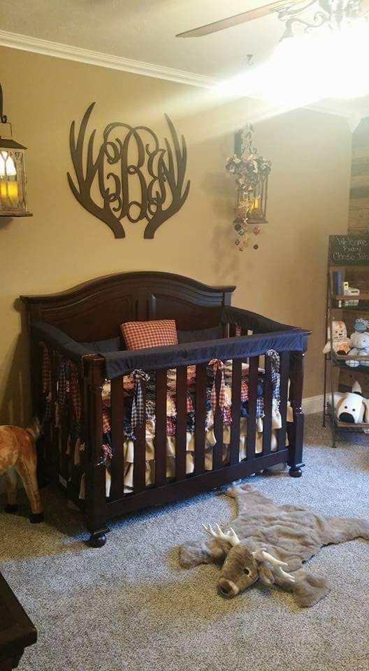 A rustic deer nursery featuring a wooden pallet accent wall, burlap blinds, burlap bed skirt and monogram antlers.