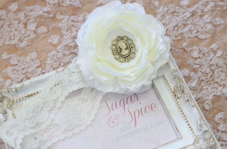 """A 3.5"""" creamy white silk flower with a vintage inspired cameo center on ivory scalloped edge lace elastic. Choose between a bronze or blue & white cameo. #craftyab #girlheadband #sugarspiceeverythingnice"""