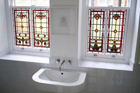 The bathroom features some of the house's original stained-glass windows, carefully restored.