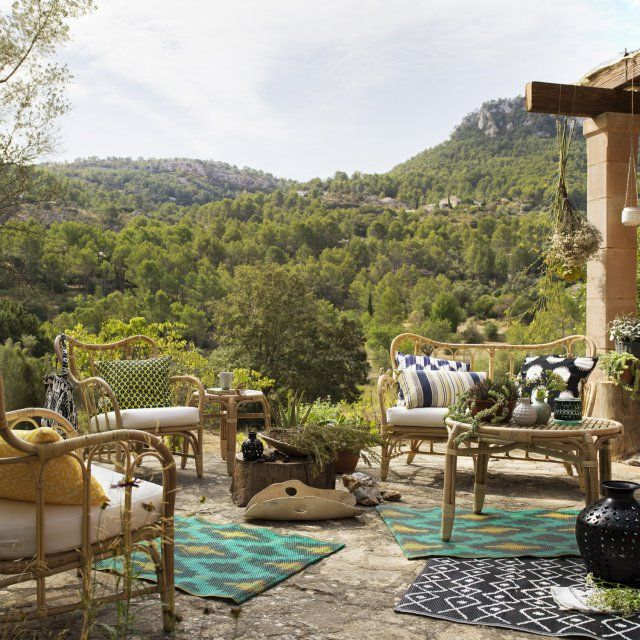 Un salon de jardin en rotin composé d'un fauteuil, une table basse et un canapé 2 places, le tout décoré de coussins et tapis colorés sur la terrasse