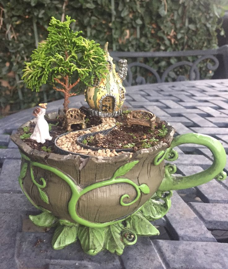 Miniature Fairy Garden - TEA CUP. DOG'S NOSE IS AT STAKE is about a dog who tends to mind his own business but always seems to find trouble -- this time a bird landed on his nose! The dog lives in a gourd cottage with his owner but no one has ever seen him. A tall tree and two gold chairs are visible; and a windy gold pathway leads to the tiny gourd cottage.  Grass was just planted. The green tea cup planter is detailed with long curly vines all around and leaves at the bottom. 2/2016
