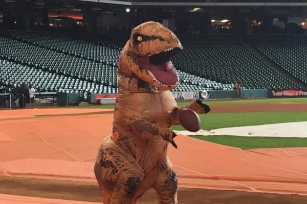 cool Houston Astros players toss football while wearing T-Rex costume