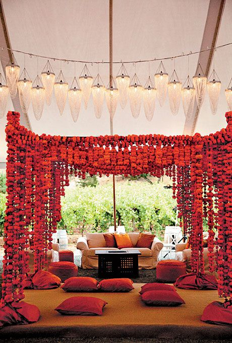 """Brides.com: . The mandap was decorated with marigold garlands and crystal pendant lights. The rentals and wedding details were arranged through Julie Atwood Events. """"It wouldn't have been the wedding of our dreams without Julie and her team,"""" says Ruchika."""