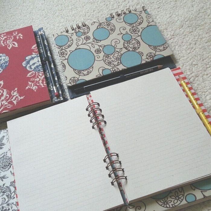 Cadernos pautados com capa de tecidos estampados.