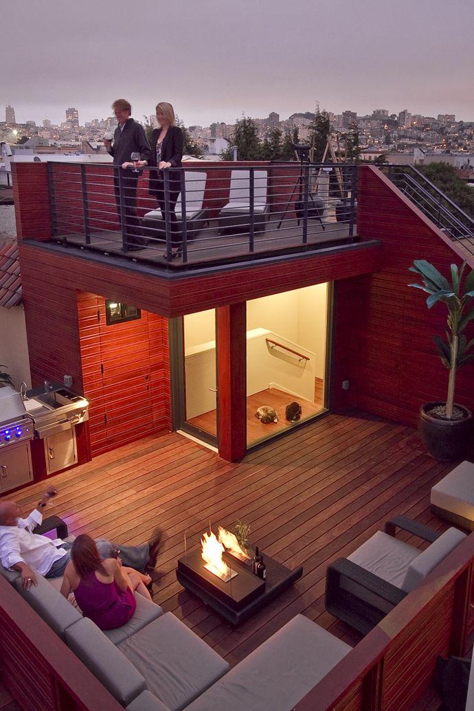 ウッドデッキの屋上テラスの屋外リビング・ダイニング 焚き火台に火を付けて夕暮れ時を楽しむ