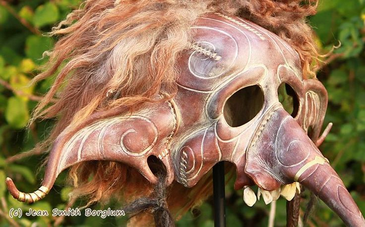 Eldir the Fire Jötnar - The troll mask is 100 % hand-made and hand-shaped of vegetable tanned leather. The other materials are grain color, acrylic paint, wild boar teeth, cow teeth, butyric acid tanned sheepskin brass bands and horn tips in the ears.