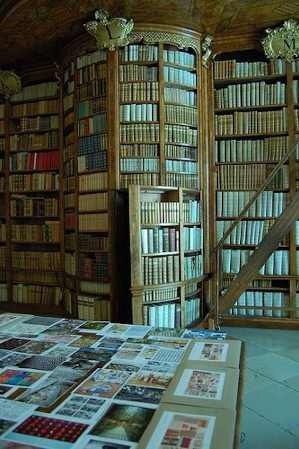 A cozy reading nook inside a rotunda of books: | 31 Beautiful Hidden Rooms And Secret Passages