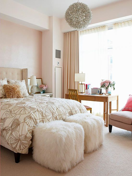 In the master bedroom, the wall behind the bed features a blushy-pink metallic paint, while the other walls, headboard, and drapery panels carry only the palest of pink hues. Gray lotus-pattern bedding and a herringbone tweed chair help cut the femininity of all of the pink. Two fur-covered ottomans at the foot of the bed and a large circular chandelier overhead add unique texture.