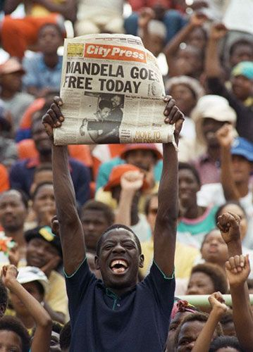 February 11, 1990: A jubilant Sowetan holds up a newspaper announcing Mandela's release at an African National Congress (ANC) rally in Soweto