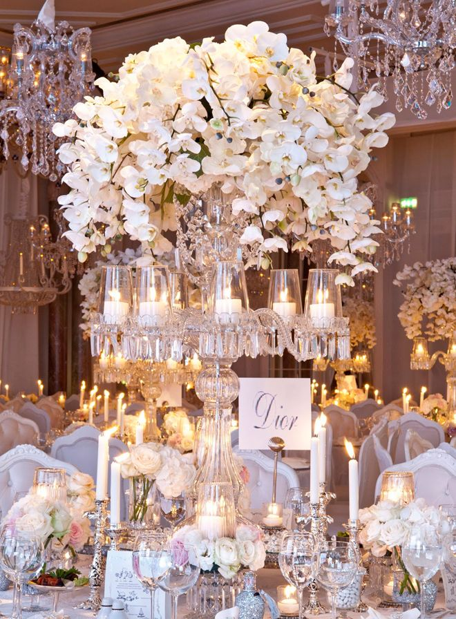 Elegant Centerpiece of Orchids using a Tall Crystal Candelabra. Visit us for Crystal Candelabras and more centerpiece ideas http://www.WedCrafts.com | Amanda@WedCrafts.com #CanDoCandelabras