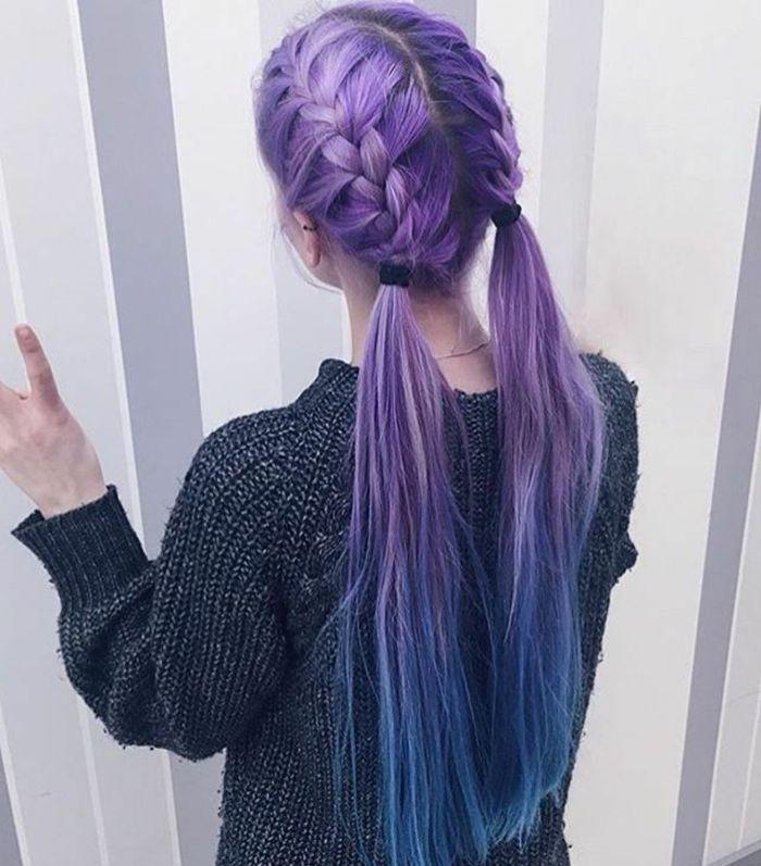 echt lange lila Haare mit blauen Spitzen, Frisur mit zwei holländischen Zöpfen seitlich am Kopf, gebunden mit zwei schwarzen Bändern, grauer Pulli mit weißen Fäden