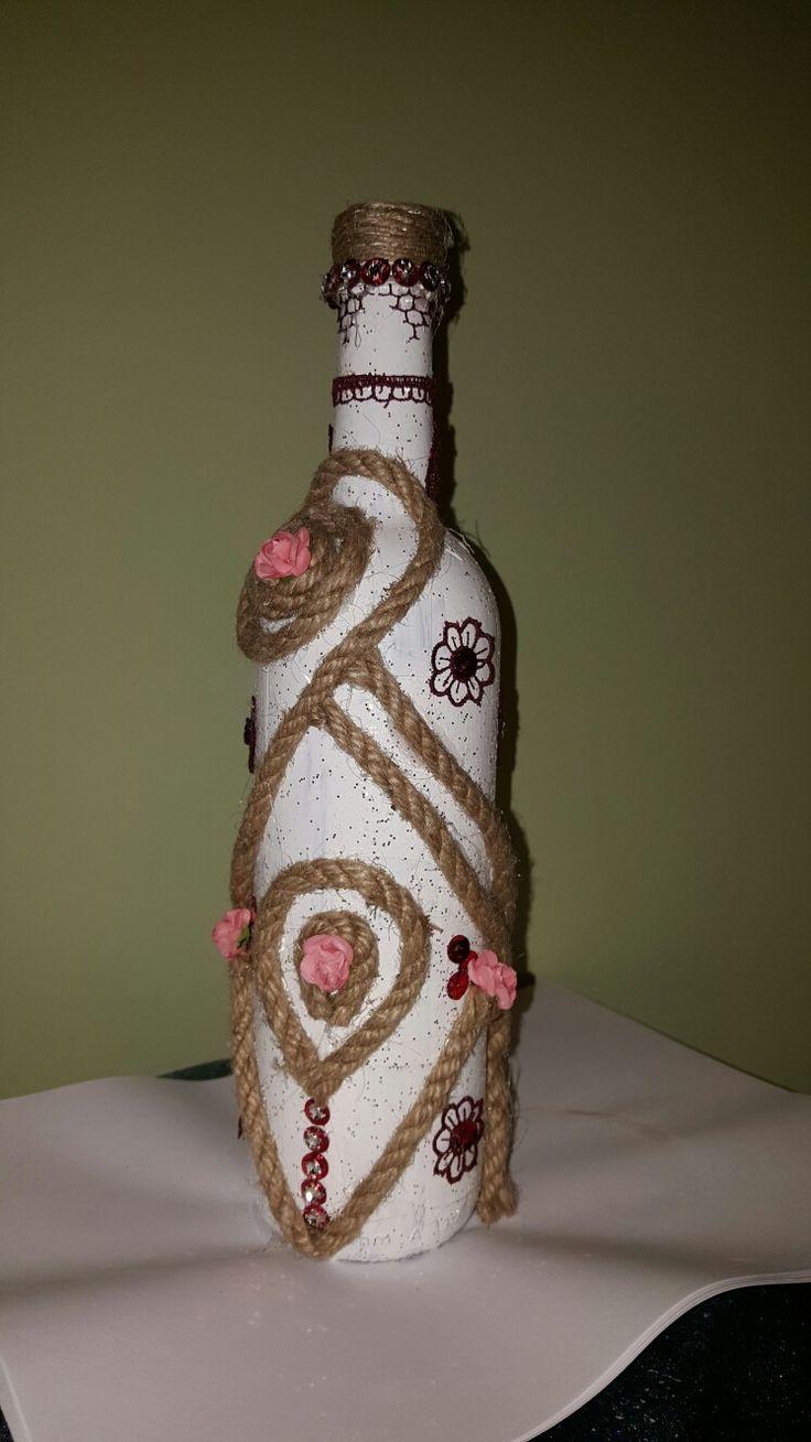 Beyaz boya ile boyayıp silikonla çiçek ve halat yapıştırdigim bir şarap şişesi