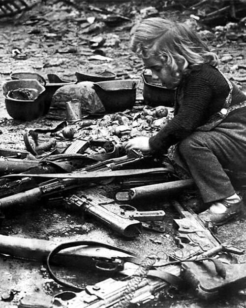 Little girl playing with guns left on streets of Berlin after war in 1945