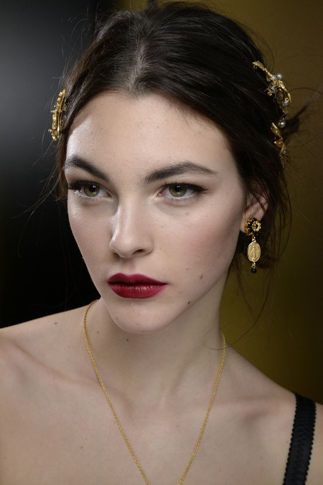 With a collection inspired by mothers, Dolce & Gabbana's fall-winter 2015 beauty looks did not shy away from their normal Italian, bombshell, glamour. Models wore their hair in elegant updos adorned with crystal clips or headbands. With Pat MacGrath on makeup, lips were in near nudes or vibrant reds. While winged eyes were also in for the fall season. Check ...
