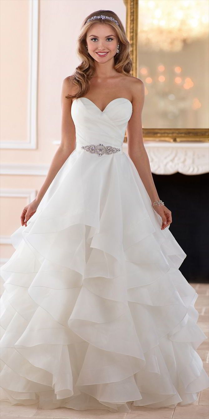 This dramatic layered skirt wedding dress from Stella York is truly a sight to behold. This classic ball gown made of Royal organza has a voluminous skirt with multiple layers that looks full but feels light and airy. The ruched organza bodice in a classic sweetheart neckline gives a sense of timelessness while the skirt is modern and fresh. Fabric covered buttons over an easy-close zipper finished the back for a comfortable fit.