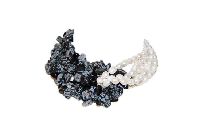 Con perlas de rio blancas y piedras blancas  y negras