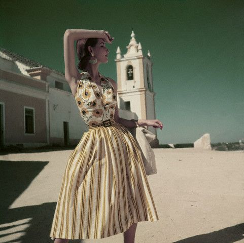 ca. 1952, Olhao, Portugal – Model standing in a courtyard in Olhao, Portugal, wearing a halter and skirt by Brigance.
