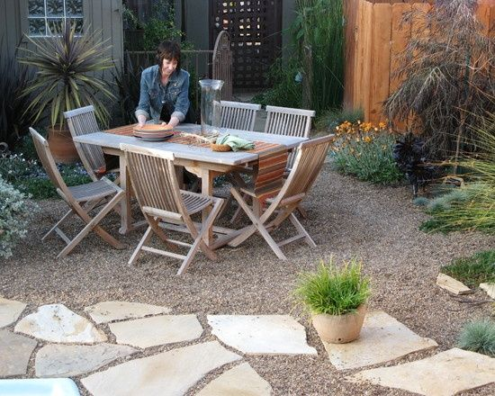 table on pea gravel with neighboring flowing flagstones and garden beds debora carl landscape design mediterranean landscape
