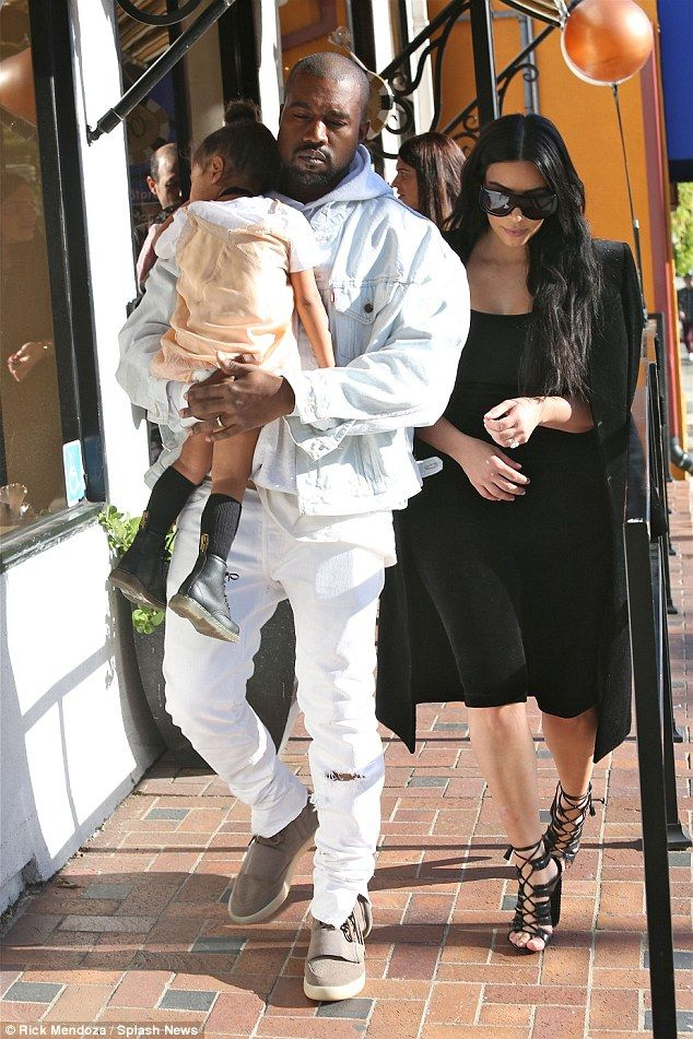 Quiet time: Rapper Kanye West carried a sleeping North West while out with wife Kim Kardashian in West Hollywood on Sunday