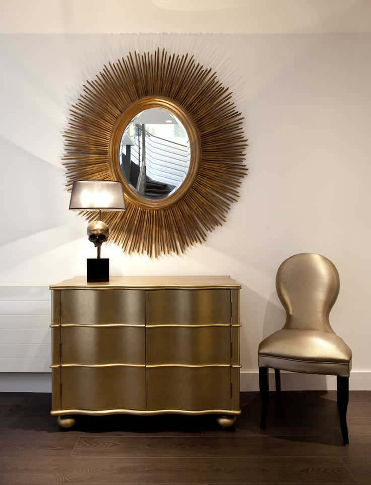 Gold oval mirror, gold chest of draws and gold chair all in the urban living interiors London showroom
