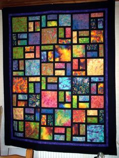 batiks and black solid for sashing and borders...looks like stained glass!