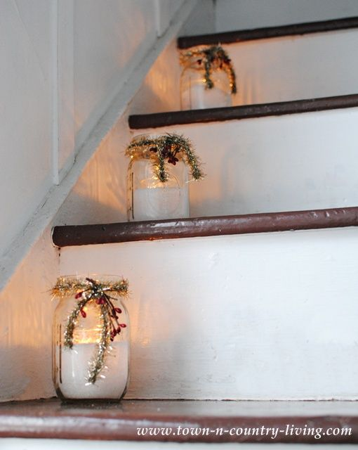 Mason Jars filled with flour for snow and a votive tucked inside. Decorate with tinsel and berries and line them up on the stairs.