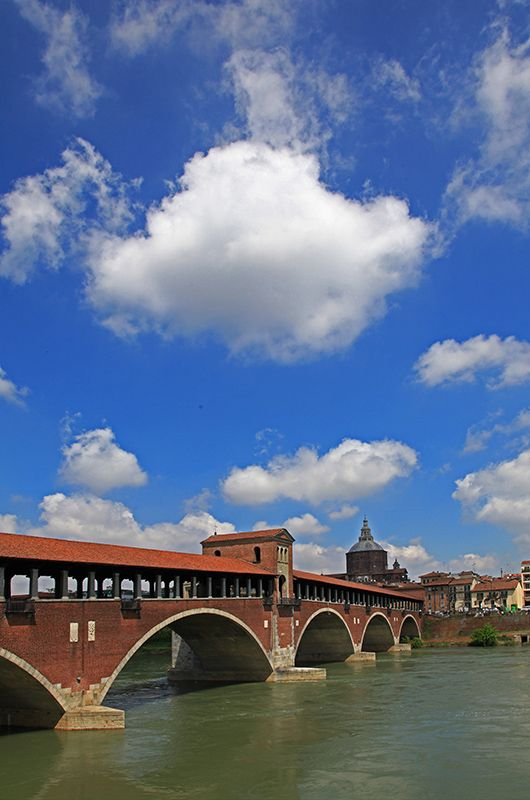Pavia's old bridge, under a sky with fluffy clouds, Italy