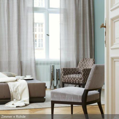 In dem Wohnzimmer zieht Ruhe durch die natürliche Farbgebung der Stoffe ein. Gardinen, Polsterstühle und der moderne Ottomane teilen sich eine Farbpalette aus …
