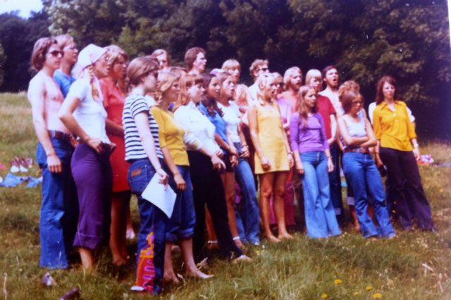 Ingeborg Rørbye, 66, København.  Billedet er taget ved en korprøve i det fri. Påklædningen var vel nærmest som andre unge menneskers idag: cowboybukser, T-shirts, korte kjoler. Til koncerterne skulle vi være lidt mere uniformerede, og det blev en lidt blød udgave: pigerne i lange bomuldsnederdele (efter eget valg) + hvide T-shirts, drengene bare i lange bukser + hvide T-shirts. Det er vist mest hårlængden og de brede bukseben, der afslører årtiet! Koret hed Musik & Ungdoms Kor (1972).