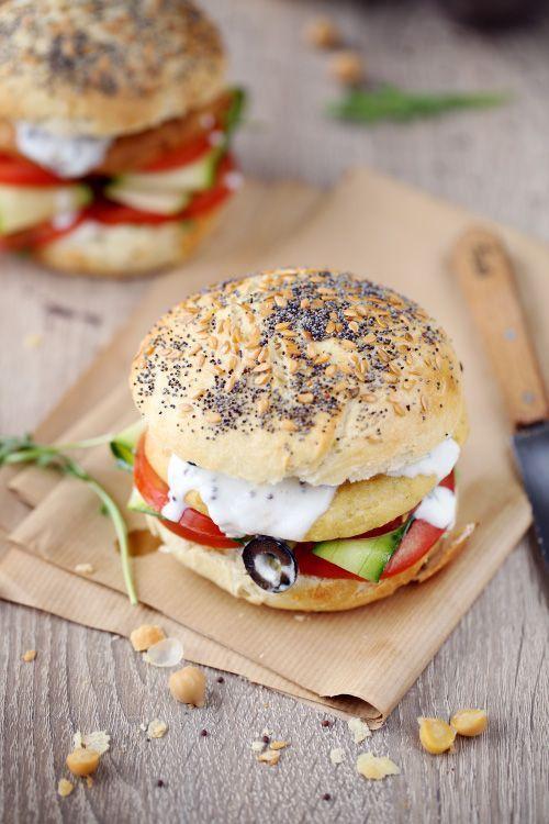 Je vous propose un hamburger végétarien garni de tomates, lamelles de courgette enrobées d'huile de sésame, d'olives et d'une galette de pois chiche maison: