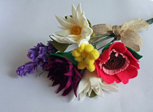 Our felt flowers are made with lots of love and care. This bunch of wild flowers are vibrant with a hot pink anemone, a deep purple Aster, white large daisies, a yellow bunch of mimosa and lilac and purple sprigs of lavender. Each flower is assemble petal by petal for a beautiful realistic look that will last for years to come. This bouquet is finished with hessian ribbon. Details: Materials: 40% Wool Felt Size: 8 inches ( bouquet tip to tip) Quantity: 1 anemone, 1 aster, 1 bunch of mimos...