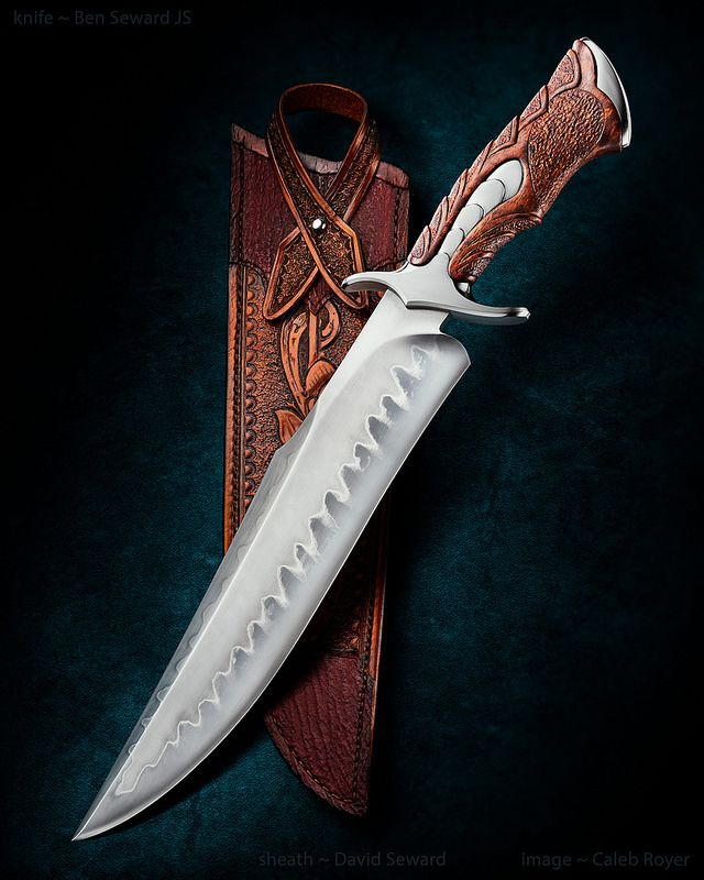 """Ben Seward """"Eclipse II"""" custom Bowie knife. 11"""", 1075 carbon steel blade with polished hamon, carved and textured stabilized African bubinga handle, carved stainless guard and pommel. Sheath by Dave Seward. Man, everything Ben makes is awesome. That handle obviously took a ton of work. Whoever got that knife is a lucky man."""