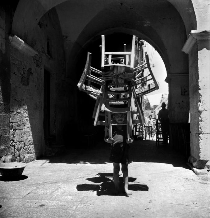 "David ""Chim"" SEYMOUR :: City of Bari, 1948 / from ""Children of Post-War Europe"" / A boy transports chairs from the carpenter's workshop to the vernishing shop. These piles of chairs are quite tricky to carry but the photographer was told the children can manage to transport about 18 chairs at a time.   #carry"
