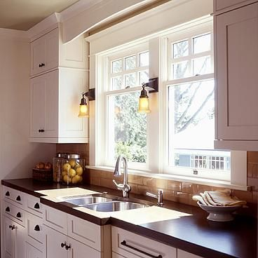 This bright, well-lit Arts & Crafts kitchen features shallow painted custom cabinetry made to fit the space. The bump-out at the sink allows the use of an inexpensive standard sink and full-size faucet. The laminate countertops are a close approximation of soapstone. The period lamps are from our favorite house part seller, Rejuvenation.