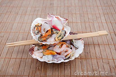 Seashells filled with fresh seafood and sticks on bamboo table.