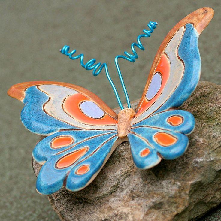Modrý+motýl+Ručně+modelovaný+motýl+z+bílé+hlíny+je+plasticky+tvarovaný,+patinovaný+oxidem,+a+dekorovaný+ef…