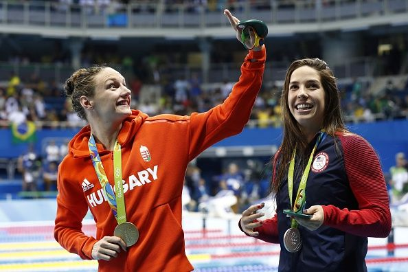 Hungary's Katinka Hosszu waves next to silver medallist USA's Madeline 'Maya' Dirado after she won the Women's 400m Individual Medley Final during...