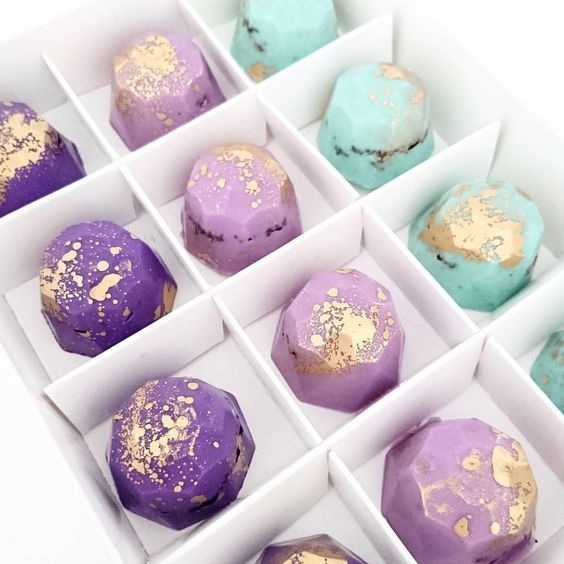 """NOW AVAILABLE TO ORDER ONLINE 12 x Chocolate Gems presented in white gift box. """"EMPRESS"""" colour pallette: violet, lilac and pastel mint green. Filled with crushed chocolate cookie and flecked with gold. Order in advance and pick up from per kitchen in Castle Hill."""