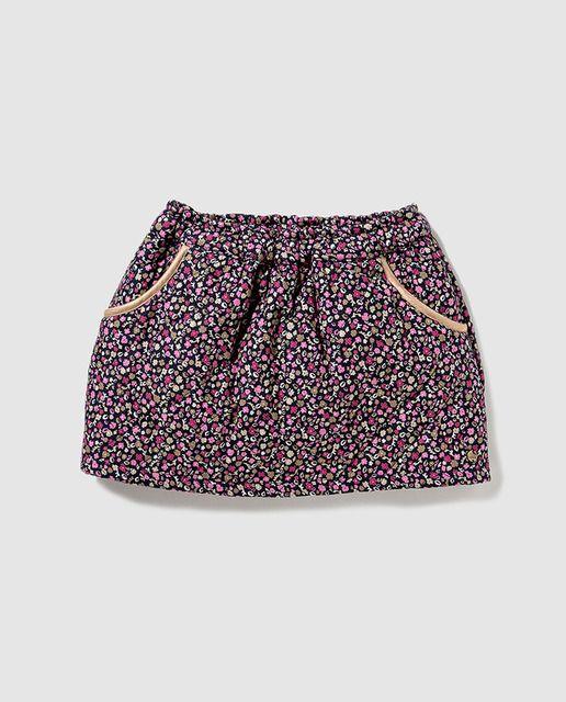 Falda corta con efecto acolchado, estampada con elástico en la cintura. Tiene dos bolsillos en el delantero con detalle de vivo dorado.