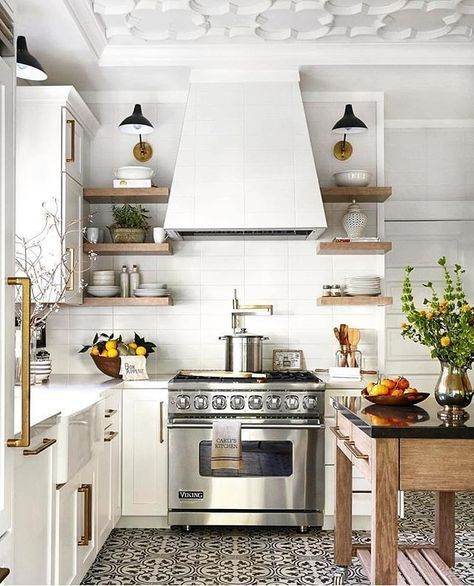Vintage modern farmhouse kitchen in white and black featuring white cabinets with antiqued brass hardware, patterned concrete tile flooring and a rustic wood island - Vintage Modern Kitchen Ideas & Decor