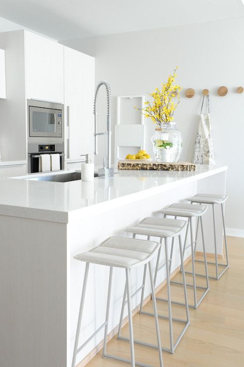 Modern kitchen features light gray walls painted Benjamin Moore Balboa Mist studded with a set of CB2 Dot Coat Hooks.