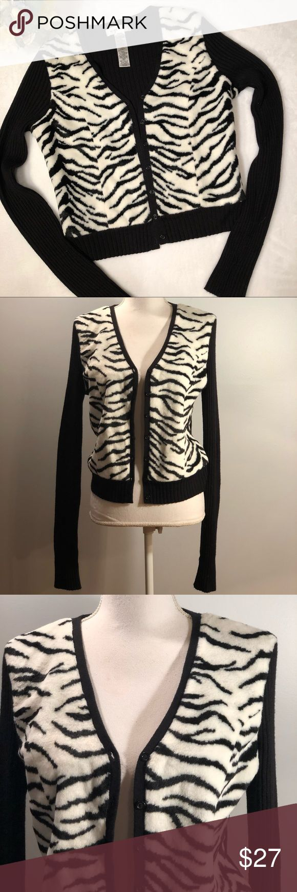 """Nine West Zebra Print Fur Panel Button Up Cardigan Nine West Zebra Print Fur Panel Button Up Caridgan. Black and white zebra print fur panels on front. Ribbed, black stretchy material. V neckline. Full button up cardigan. Long sleeves. Size large. EUC, excellent used condition. No flaws. Measurements taken laid flat. 15"""" shoulder width, 19.5"""" bust, 22"""" length. Nine West Sweaters Cardigans"""