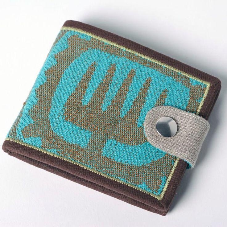Авторский мужской кошелек ручной работы от отечественного бренда Yak Faino, сшитый вручную мастером из двух видов натуральной ткани – лен и хлопок. Лицевая внешняя сторона имеет этнический принт со стилизованным знаком-пиктограммой голубого цвета сером на фоне, снабжена фронтальной кнопочной з