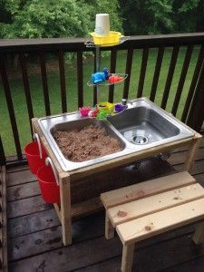 This is a DIY water table for kids made from a thrift store kitchen sink! They used pallet wood around it and even put in a couple of knobs for the buckets on the side. My kids would love this!