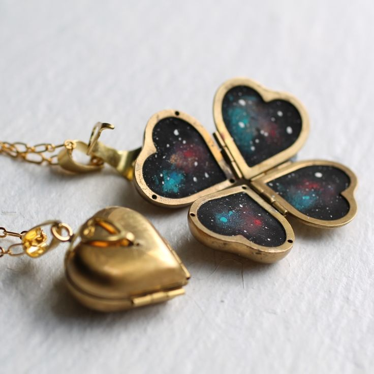 This beautifully designed vintage locket features a rounded heart shape, with an ornate clasp that opens out to reveal space four little paintings of space! You can carry around your own secret universe, hidden inside! Each one is handpainted from scratch and is totally unique.The locket is solid brass and the fine chain and clasps are gold plated brass.Please note that these lockets are vintage brass, and may have some very fine scratches on the inner panels or rear. Th...
